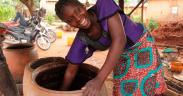 Madame Rita, propietaria de una cervecería familiar en Benin, sirviendo cerveza de grandes vasijas de arcilla